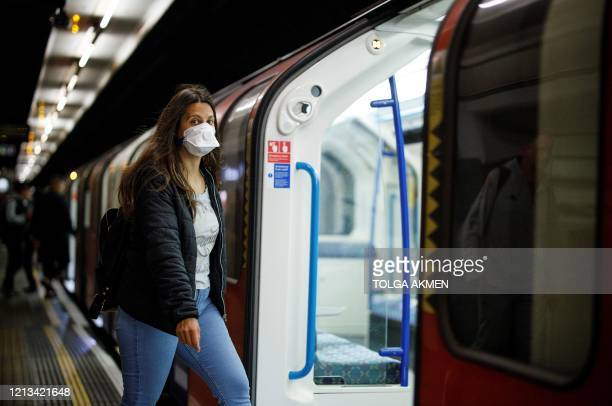 Commuters wear PPE , including a face mask as a precautionary measure against COVID-19, travel on a TfL victoria line underground train towards...