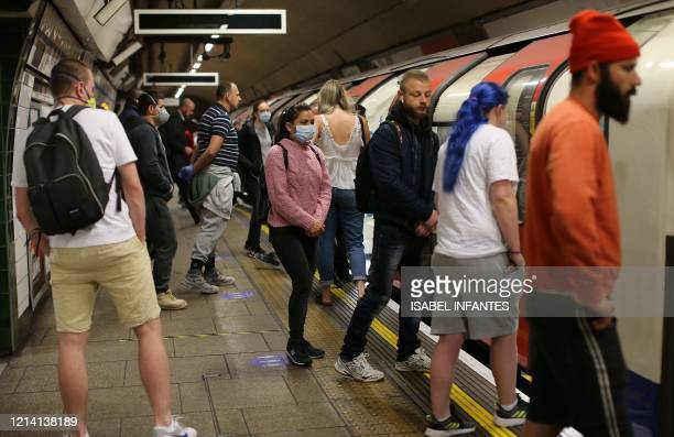 Commuters wear PPE , including a face mask as a precautionary measure against COVID-19, as they travel on a TfL Victoria line underground train...