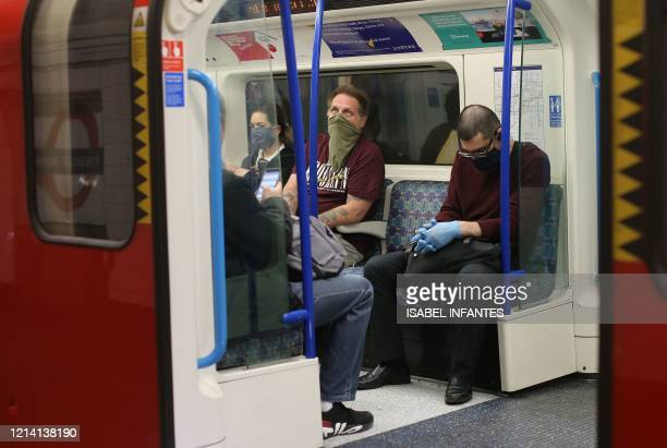 Commuters wear PPE including a face mask as a precautionary measure against COVID19 as they travel on a TfL Victoria line underground train towards...