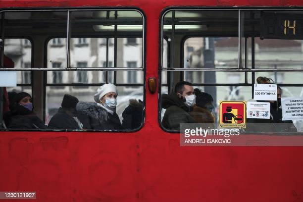 Commuters wear protective face masks while taking a tram ride during the COVID-19 pandemic in Belgrade, on December 14, 2020. - Serbia is witnessing...