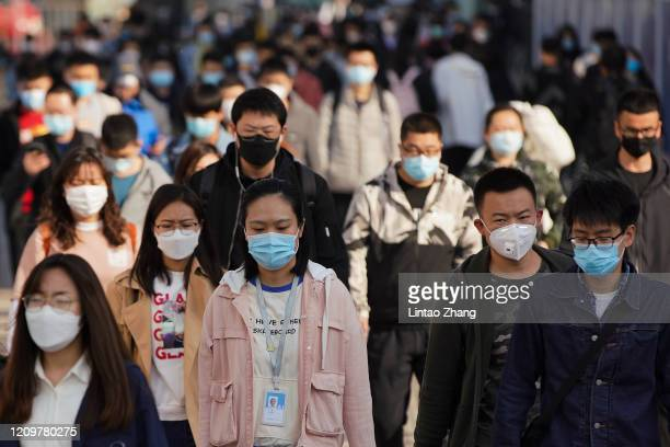 Commuters wear protective masks as they exit a train at a subway station during Monday rush hour on April 13, 2020 in Beijing, China. According to...