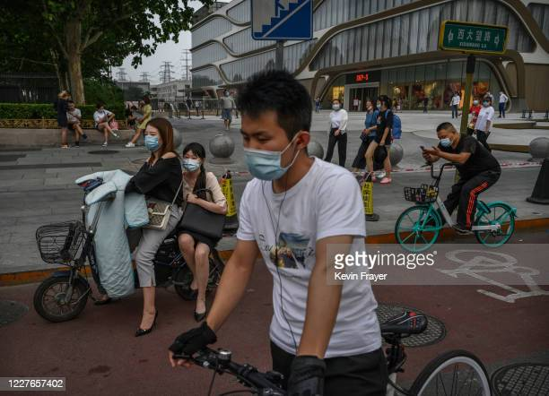 Commuters wear protective masks as they wait to cross an intersection during rush hour on July 17 2020 in Beijing China Chinas economy returned to...