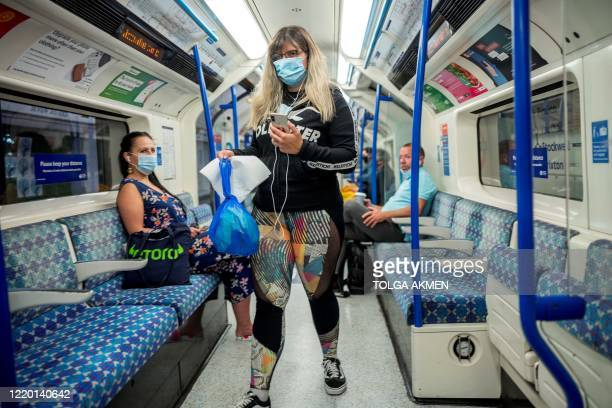 Commuters wearing a face mask travel on TfL Victoria Line underground train carriages heading towards central London on June 15 2020 after new rules...