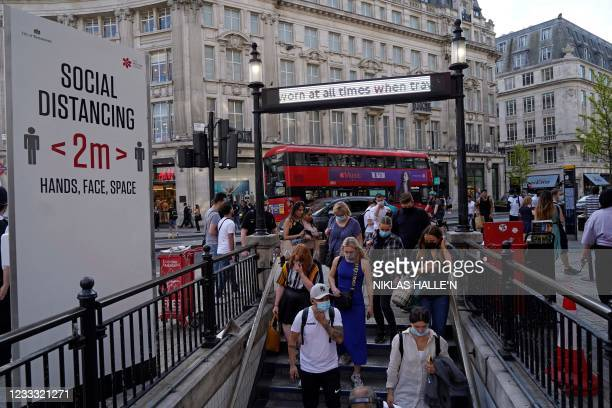 Commuters wearing face coverings due to Covid-19, enter Oxford Circus London Underground station in central London on June 7, 2021. - The Delta...
