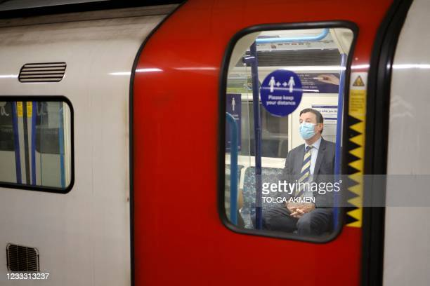 Commuters wearing face coverings due to Covid-19, travel on a Transport for London Underground train in central London on June 7, 2021. - The Delta...