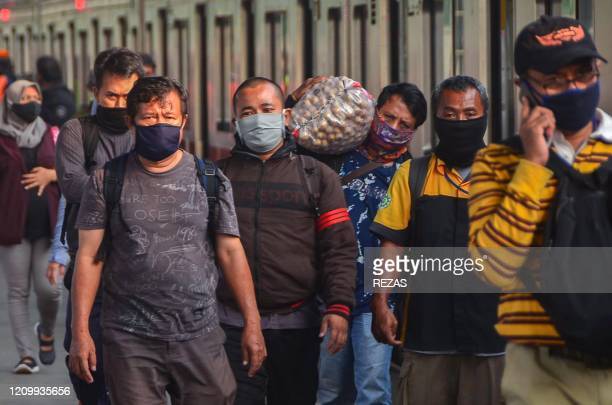 Commuters wearing face masks amid concerns over the COVID19 coronavirus walk at a train staiton in Bekasi West Java on April 15 2020