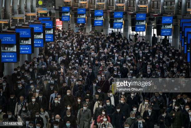 Commuters wearing face masks make their way to work on March 26, 2020 in Tokyo, Japan. Tokyo Governor Yuriko Koike held a press conference last night...