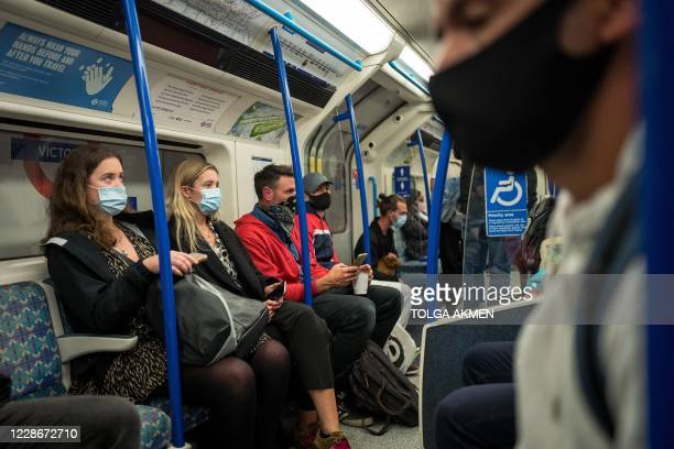 Commuters wearing face masks or covering due to the COVID-19 pandemic, sit aboard a Victoria Line London underground tube train as they travel during...