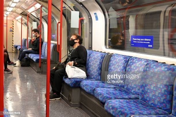 Commuters wearing face masks or coverings travel on a TfL Central Line Underground train carriage towards central London on June 15, 2020 after new...