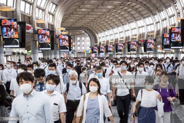 Commuters wearing face masks pass through Shinagawa train station on July 10 2020 in Tokyo Japan Tokyo confirmed 243 new Covid19 coronavirus...