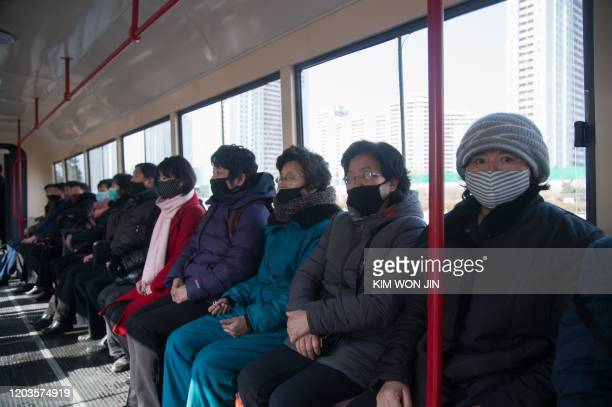 TOPSHOT Commuters wearing face masks ride a tramcar in Pyongyang on February 26 2020 The novel coronavirus has killed over 2700 people and infected...