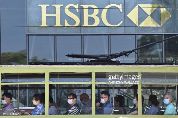 Commuters wearing face masks travel on a tram past HSBC signage displayed outside the banks local headquarters in Hong Kong on April 28, 2020. - The...