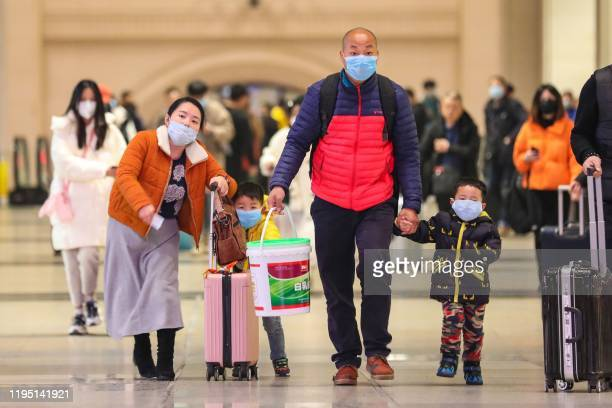Commuters wearing face masks walk in Hankou railway station in Wuhan in China's central Hubei province on January 21 2020 Asian countries on January...