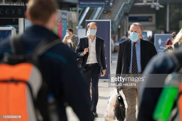 Commuters wearing face masks walk through the concourse at Waterloo Station in London on June 15, 2020 after new rules make wearing face coverings on...