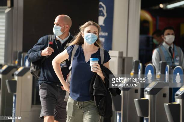 Commuters wearing face masks walk through the ticket barriers at Waterloo Station in London on June 15, 2020 after new rules make wearing face...