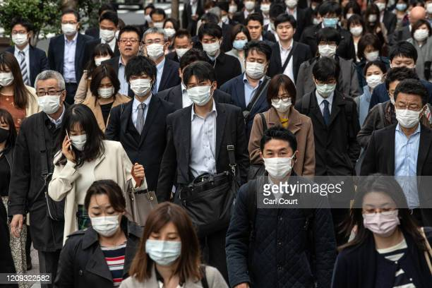 Commuters wearing face masks walk to work the day before a state of emergency is expected to be imposed on April 7, 2020 in Tokyo, Japan. Japans...