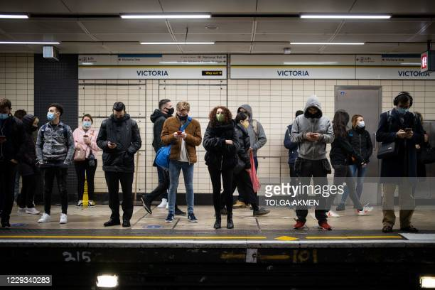 Commuters wearing masks because of the coronavirus pandemic wait for a tube train at Victoria Underground Station in central London on October 29,...