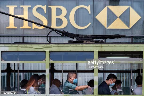 Commuters wearing masks ride on a tram as it passes in front of the British multinational banking and financial services holding company HSBC...