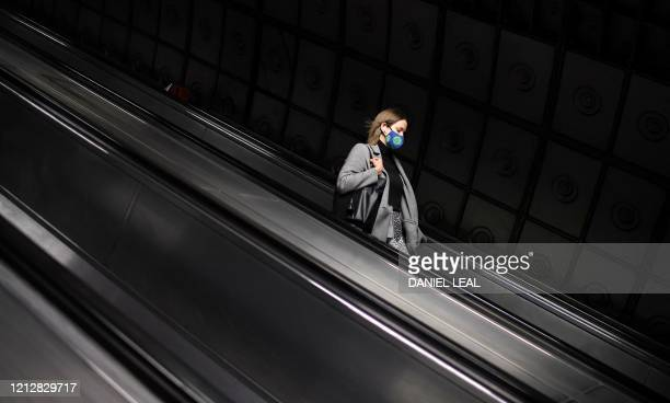 Commuters wearing PPE , including a face mask as a precautionary measure against COVID-19, travel trhough Waterloo Train Station in central London on...
