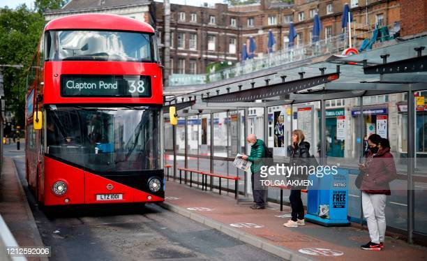 Commuters wearing PPE including a face mask as a precautionary measure against COVID19 wait to catch a red London bus in the morning rush hour on May...