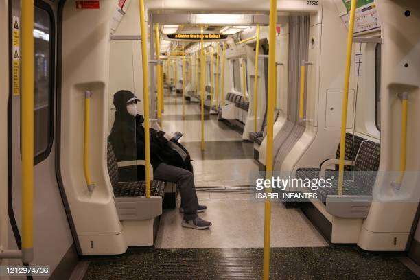TOPSHOT Commuters wearing PPE including face masks as a precautionary measure against COVID19 travel by public transport during the evening 'rush...