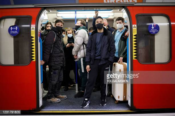 Commuters wearing protective face coverings to combat the spread of the coronavirus, wait for the doors of a tube-train to close during the evening...