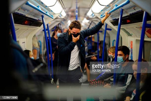 Commuters wearing protective face coverings travel on Victoria line at rush hour in central London on September 23, 2020. - Britain on Tuesday...