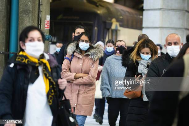 Commuters wearing protective face masks arrive at Gare Montparnasse railway station in Paris France on Tuesday May 12 2020 The Paris metro authority...