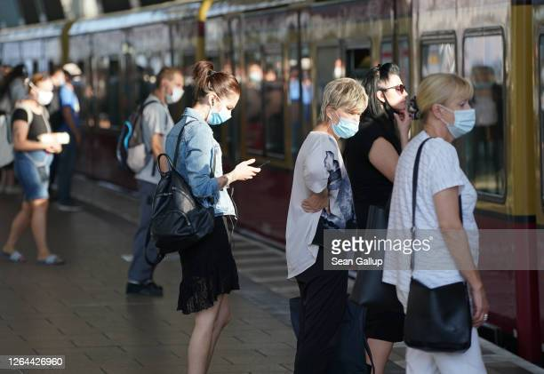 Commuters wearing protective face masks board a train during the novel coronavirus pandemic on August 07, 2020 in Berlin, Germany. Coronavirus...