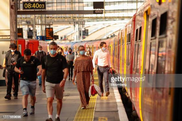 Commuters, wearing protective face masks, walk along a platform after arriving at London Waterloo station in London, U.K., on Monday, Aug. 3, 2020....