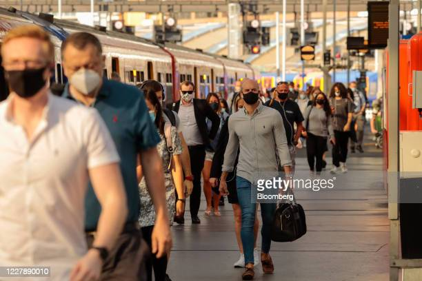 Commuters wearing protective face masks walk along a platform after arriving at London Waterloo railway station in London UK on Monday Aug 3 2020...