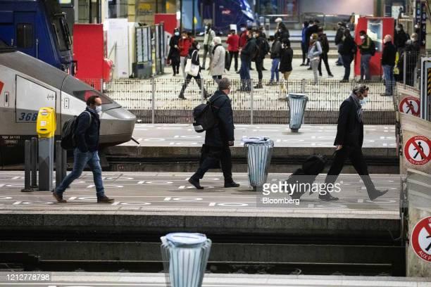 Commuters wearing protective face masks walk over social distancing markers on a platform after arriving at Gare Montparnasse railway station in...