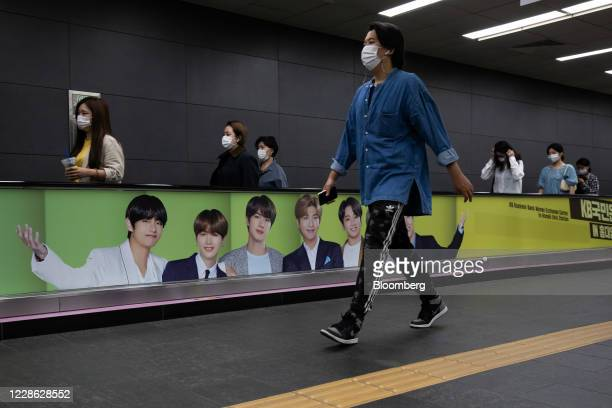 Commuters wearing protective masks ride on a travelator featuring an advertisement for K-pop boy band BTS at a subway station in Seoul, South Korea,...