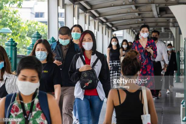 Commuters wearing protective masks walk along a pedestrian bridge in Bangkok Thailand on Wednesday Sept 2 2020 Thailand has reported zero...