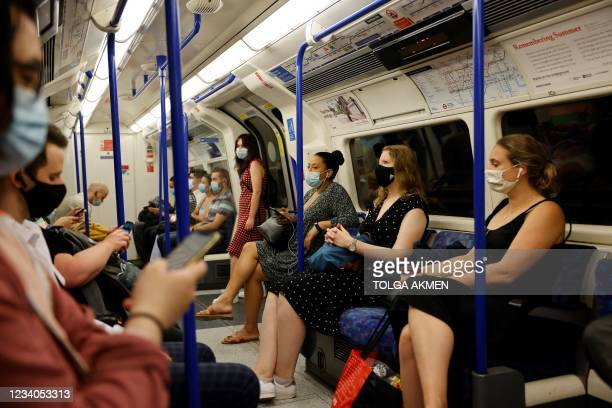 Commuters with facemasks travel on the London Underground in London on July 19, 2021. - England lifts virtually all of its coronavirus restrictions...