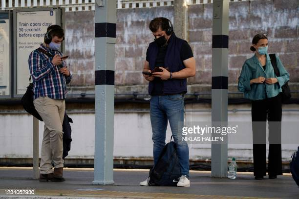 Commuters with facemasks wait for trains at Richmond station in southwest London on July 19, 2021. - England lifts virtually all of its coronavirus...
