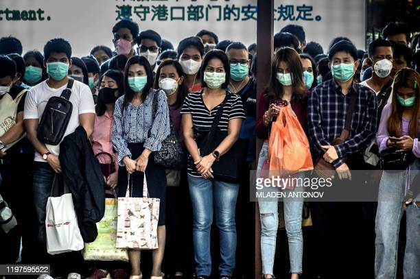 TOPSHOT Commuters with protective facemasks wait to board a canal boat at Pratunam Pier in Bangkok on January 30 2020 A Thai surgical mask factory...