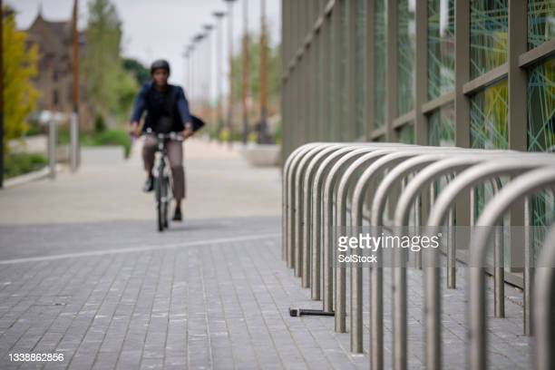 commuting businessman arriving at work on his bicycle - green blazer stock pictures, royalty-free photos & images
