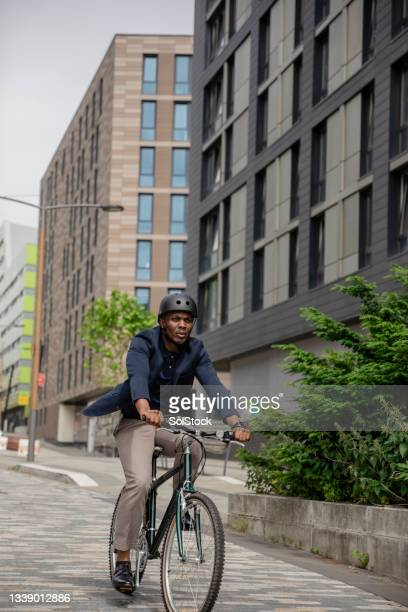 commuting businessman cycling his bicycle - green blazer stock pictures, royalty-free photos & images