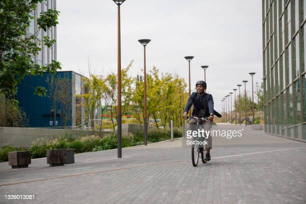 commuting businessman cycling to work - green blazer stock pictures, royalty-free photos & images
