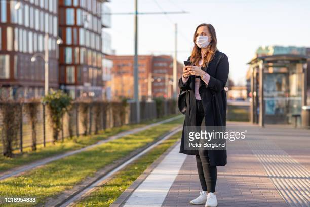 commuting woman wearing a face mask - illness prevention stock pictures, royalty-free photos & images