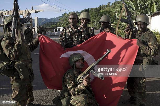 Comoran and Tanzanian African Union troops pose with an Anjouanese flag taken from one of the main barracks of the Anjouanese Gendarmes in Mutsamudu...