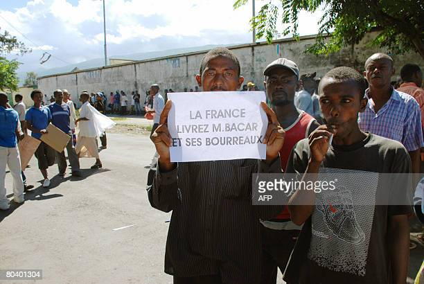 A Comoran man shows a sign as he and other protestors march towards the French embassy on March 27 2008 demanding that ousted rebel leader Mohamed...
