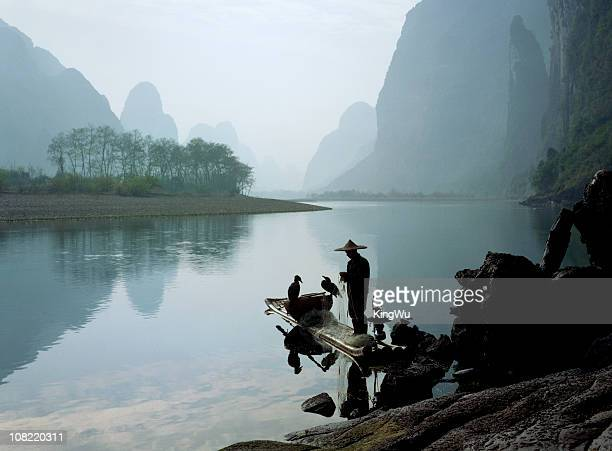 Comorant Birds Sitting on Fisherman's Boat in Li River