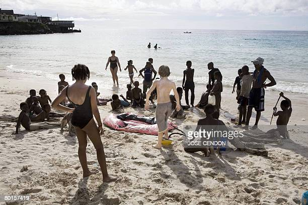 Comorian children look at a tourist inflating a pneumatic raft on March 7 2008 on a beach in Moroni capital of the Union of Comoros The government of...