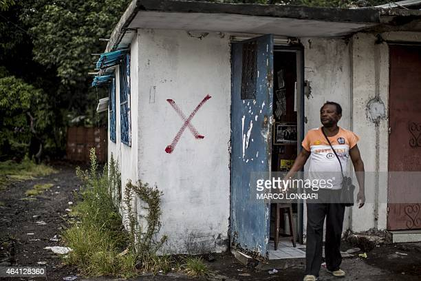 A Comorian from the island of Anjouan leaves his shop in the capital Moroni on Grande Comore island on February 22 2015 which has been marked with a...
