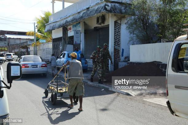 Comoros Armed Forces members patrol walk in the streets as traders and vendors work at the Market of Mutsamudu on the Comoros island of Anjouan on...
