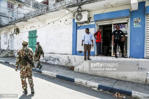 Comoros army soldiers patrol as a security guard stands outside a just reopened convenience store in Mutsamudu on October 21 2018 The Comoros...