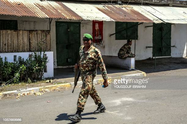 Comoros army soldiers patrol in front of a shut store doors in Mutsamudu on October 21 2018 The Comoros military on October 20 regained control of...