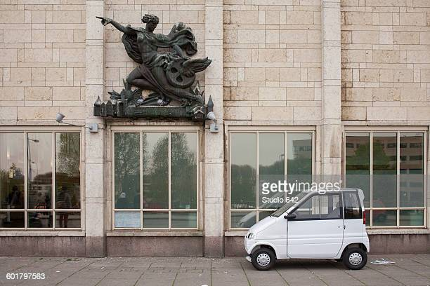 compact car parked under sculpture on building - compact car stock photos and pictures